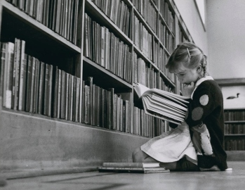 young girl reading black and white